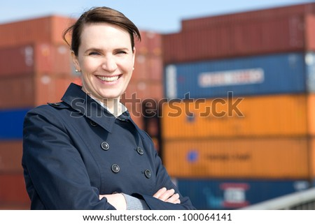Happy business woman in front of cargo container terminal