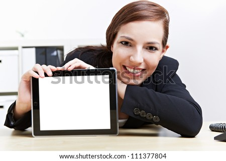 Happy business woman in her office presenting a tablet computer