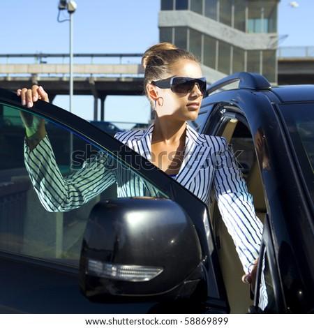 happy business woman in sunglasses near the car against city bridge