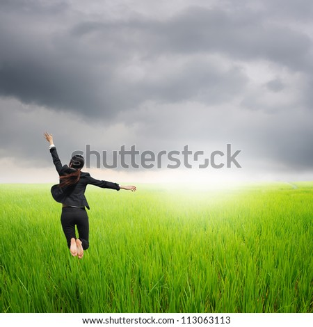 Happy business woman jumping in green rice field and rainclouds