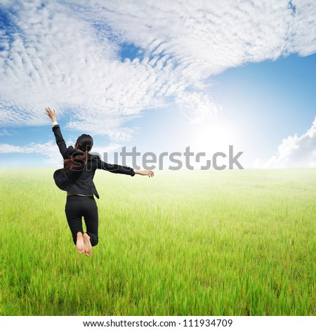 Happy Business woman jumping to clouds sky in grassland