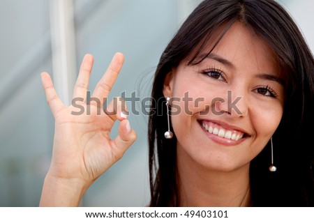 Happy business woman making an ok sign