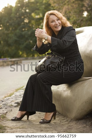 happy business woman resting after successful transaction in the park