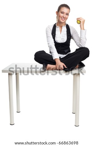 Happy business woman sit on a table and hold apple