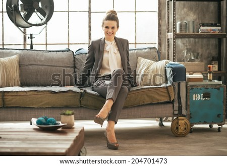 Happy business woman sitting in loft apartment on couch