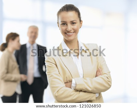 Happy Business woman standing in the office and smiling. Her colleagues standing in the background.
