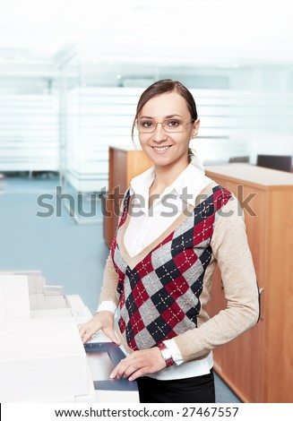 happy business woman standing near copier in modern office environment
