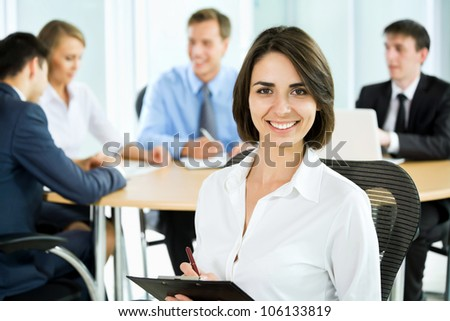 Happy business woman with colleagues at the back