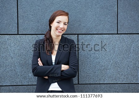 Happy business woman with her arms crossed leaning on a wall - stock photo