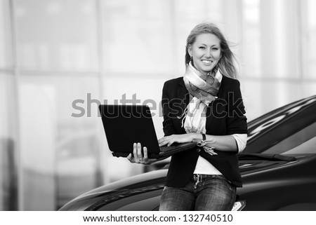Happy business woman with laptop sitting on the car