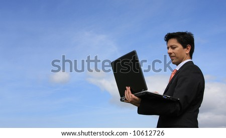 Happy businessman analyzing a financial report on his laptop