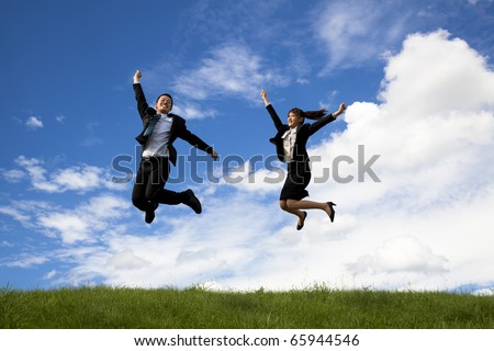 Happy Businessman and businesswoman jumping on a green meadow
