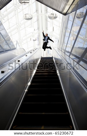 Happy businessman and Escalator in the modern building - stock photo