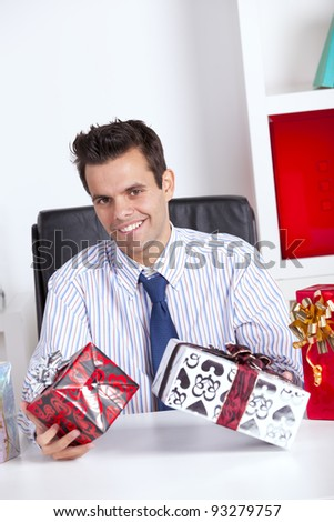 Happy businessman at his office giving valentine day gifts