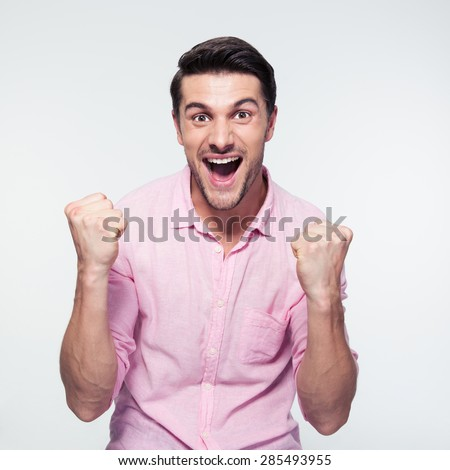 Happy businessman celebrating his success over gray background. Looking at camera