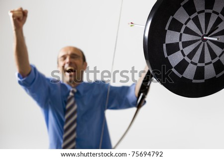 Happy businessman cheering as he hit the target with bow and arrow symbolizing successful business.