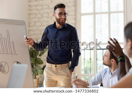 Happy businessman coach speaker and diverse team people discuss business presentation at corporate training, smiling male manager presenter work with flip chart talk to audience at lecture workshop
