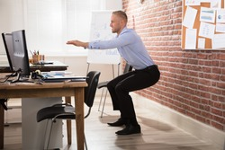Happy Businessman Doing Exercise In Front Of Computer At Office