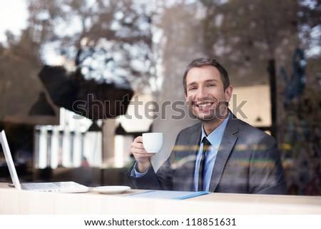 Happy businessman drinking coffee in restaurant.