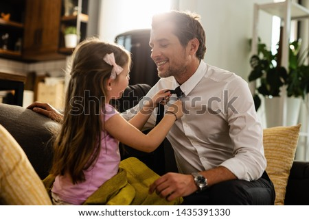 Happy businessman enjoying while daughter is adjusting his necktie at home.