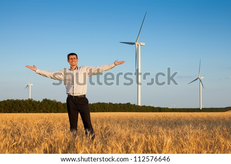 happy businessman (farmer) standing in a wheat field and smiling over background of blue sky and white wind turbine with hands raised - stock photo
