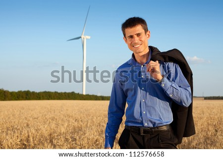 happy businessman (farmer) standing in a wheat field and smiling over background of blue sky and white wind turbine