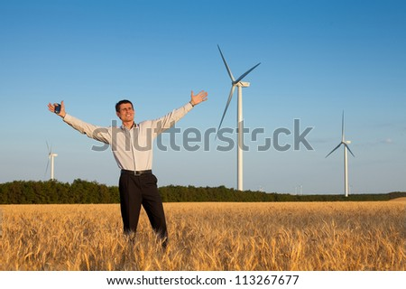 happy businessman (farmer) standing in a wheat field and smiling over background of blue sky and white wind turbine with hands raised