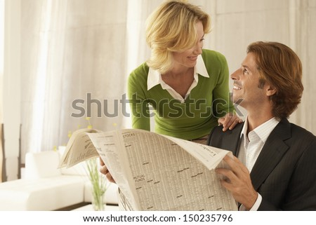 Happy businessman holding newspaper while looking at female coworker in office