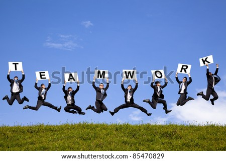 happy businessman holding teamwork text and jumping on the green field