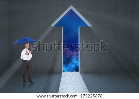 Happy businessman holding umbrella against arrow door in dark room