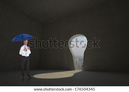 Happy businessman holding umbrella against keyhole door in dark room