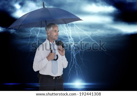 Happy businessman holding umbrella against stormy dark sky with lightning bolts