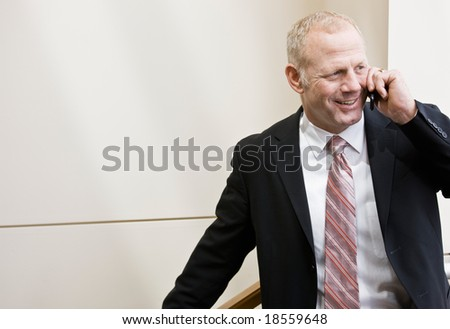 Happy businessman in full suit and tie talking on cell phone