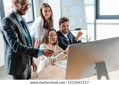 happy businessman in glasses holding pen and looking at computer monitor near multicultural coworkers in office