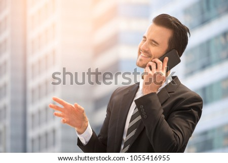 Happy businessman in suit and speaking on smart phone with office building background