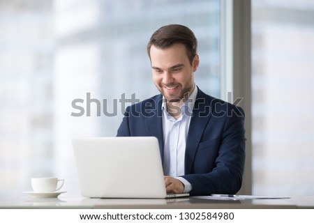 Happy businessman in suit using laptop software for business at workplace, smiling male executive worker typing business email on computer at corporate work desk, surfing web, online job in office