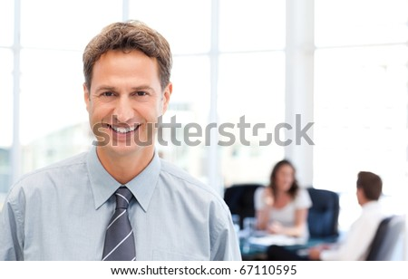 Happy businessman in the foreground while his team is working at a table
