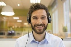 Happy Businessman in the office on the phone, headset, Skype. looking camera