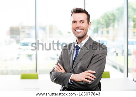 Happy businessman in the office standing with crossed arms