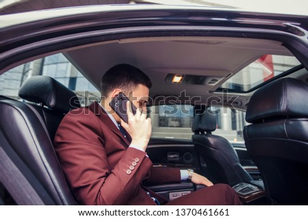 Happy businessman is talking on mobile while driving in his limo car