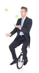 Happy Businessman Juggling Ball Sitting On Unicycle