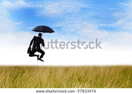 Happy businessman jumping on the meadow with umbrella
