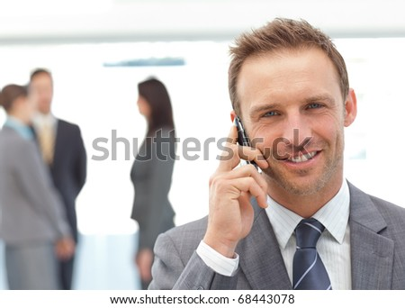 Happy businessman on the phone while his team working on the background