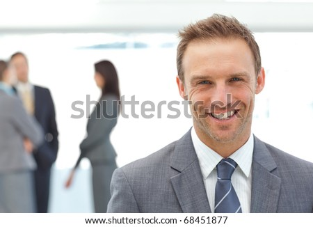 Happy businessman posing in front of his team while working on the background - stock photo
