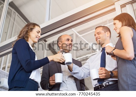 Happy businessman pouring coffee to his colleagues in meeting room. Smiling group of businessmen and businesswoman relaxing. Low angle view of formal business team take a coffe break after work. #770245435