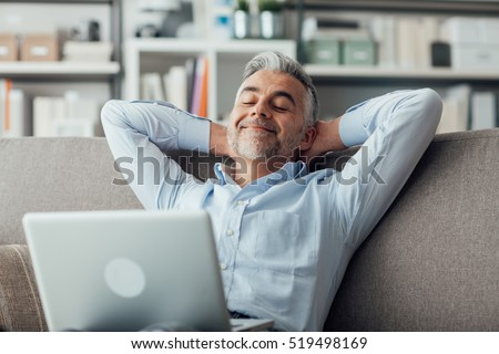 Happy businessman relaxing at home on the couch with a laptop on his lap, he is sleeping with hands behind head