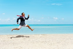 Happy businessman running away from office work on the beach. Summer vacation concept.