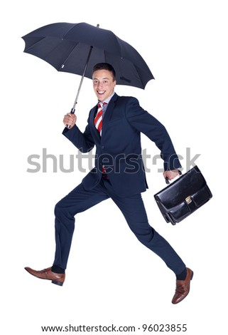 Happy businessman running with a briefcase and umbrella - stock photo
