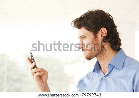 happy businessman sending or reading an message on a mobile phone