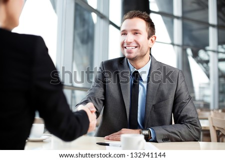 Happy businessman shaking hand with businesswoman.
